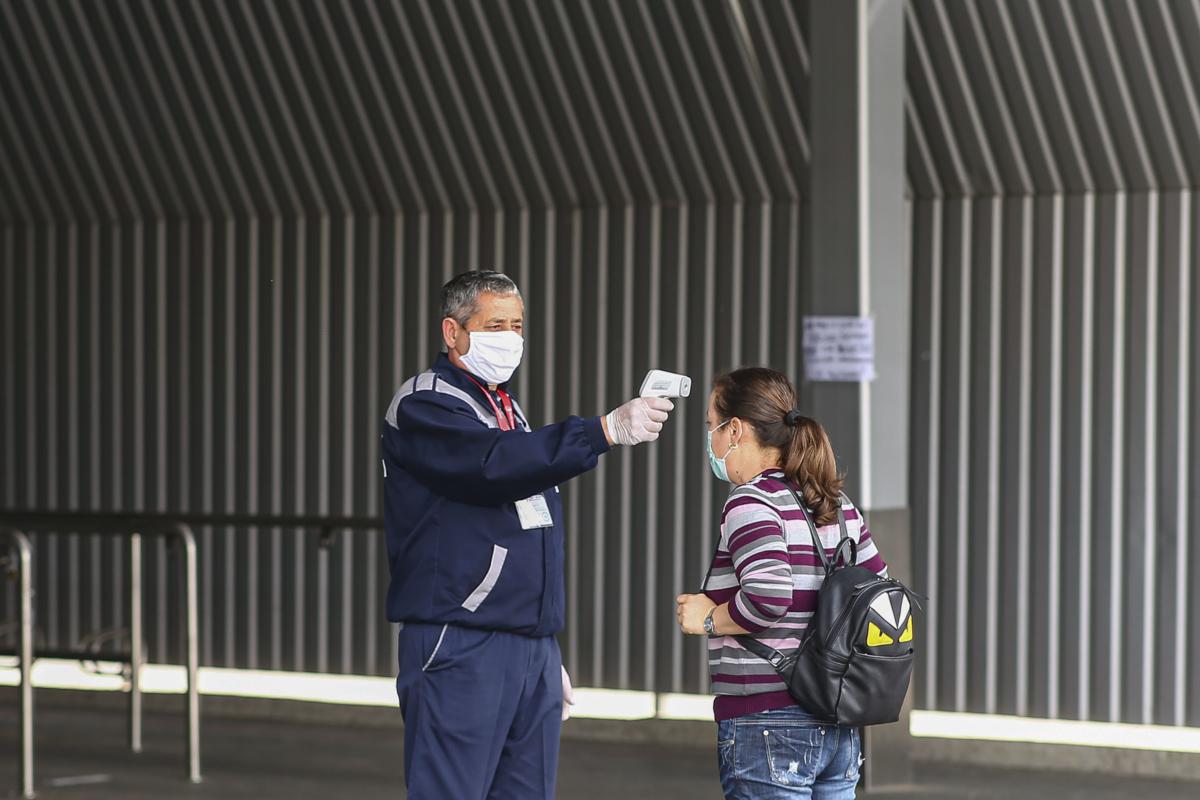 Un agent de paza de la un supermarket masoara temperatura clientilor la intrarea in magazin, luni 18 mai 2020, Timisoara.